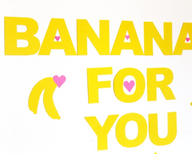 bananas-for-you-yellow-valentines-day-party-kid-birthday-hearts This Valentine's Day party is simple, and a bright dose of yellow sunshine in the middle of a snowy, cold winter. It's just what we needed, and it's just what our kids needed to celebrate love this Valentine's Day. Love comes in all shapes and forms, and we try to teach them what love means everyday. Love for themselves and love for others. It's wonderful when the sibling bickering subsides and they can hug, kiss and play with one another.  We captured it on camera, so next time they are fighting, we can remind them how much they love each other.  Banana's For You stemmed from a recent find similar to those Silly Bandz we were obsessed with. The tiny banana bracelets are going to be our kids Valentine's this year, but we wanted to have a little extra fun at home, too. It was everything banana, including the color yellow, banana ice cream, banana cut-out details, and banana bracelets.  bananas-for-you-yellow-valentines-day-party-kid-birthday-silly-bandz  Materials:  Astrobrights Paper, yellow and pink yellow washi tape banana bracelets X-acto knife Double-sided tape bowls or ice cream pint containers Directions:  Cut out the letters for Banana's For You. We used our amazing Silhouette Electronic cutting tool to cut out the letters, bananas, hearts and arrows. bananas-for-you-yellow-valentines-day-party-kid-birthday-hearts  Find a wall and use washi tape to hang the letter and bananas. bananas-for-you-yellow-valentines-day-party-kid-birthday-hearts-cupids-arrow     bananas-for-you-kid-party-valentines-day-diy-yellow-banana-pink-hearts  For the placemats, trace a banana on yellow paper with a black sharpie. Fill in the ends and lines in the middle with black marker. Use an X-acto knife to cut the side of the top-half of the banana and the line down the middle, half-way down. This will be the 'peel' effect. Place double-sided tape on all 4 corners and tape to a sheet of pink paper. Draw the name of the chil