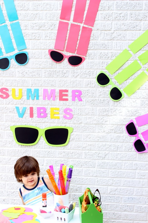 summer-vibes-paper-backdrop-colorful-sunnglasses-arched-like-a-rainbow-kids-playing-and-crafting-on-a-white-picnic-bench