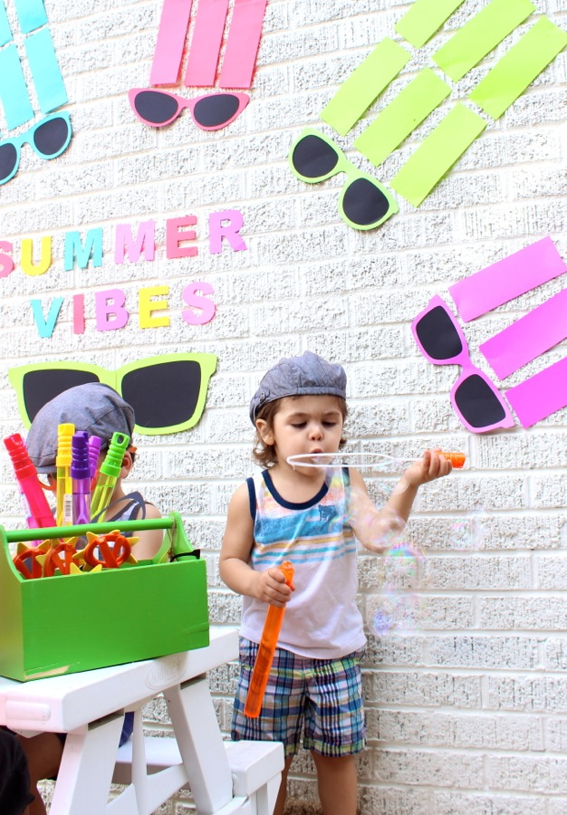 summer-vibes-paper-backdrop-colorful-sunnglasses-arched-like-a-rainbow-kids-playing-and-crafting-on-a-white-picnic-bench-and-blowing-bubbles