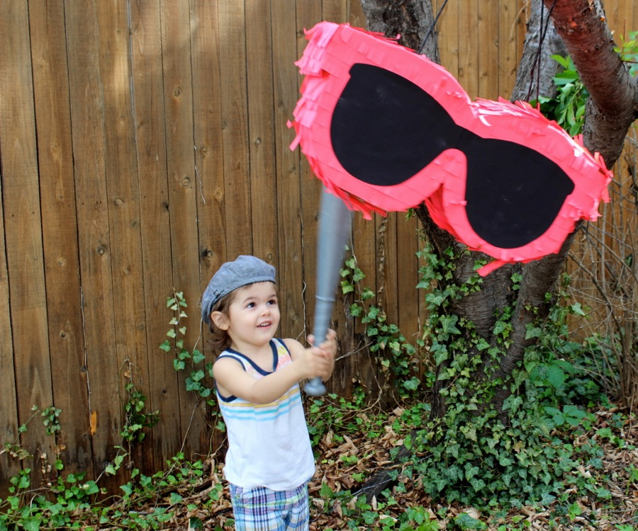 diy-sunglasses-pinata-black-and-bright-coral-gigantic-sunglasses-boy-hitting-pinata