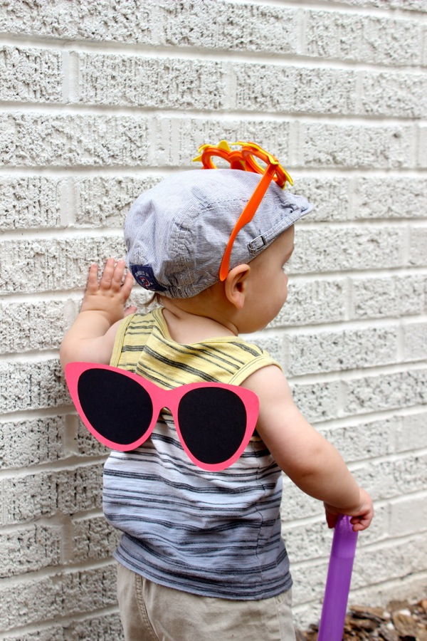 baby-boy-with-sunglasses-on-his-back-and-a-newsboy-hat