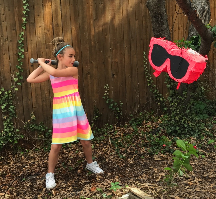 diy-sunglasses-pinata-black-and-bright-coral-gigantic-sunglasses-girl-hitting-pinata
