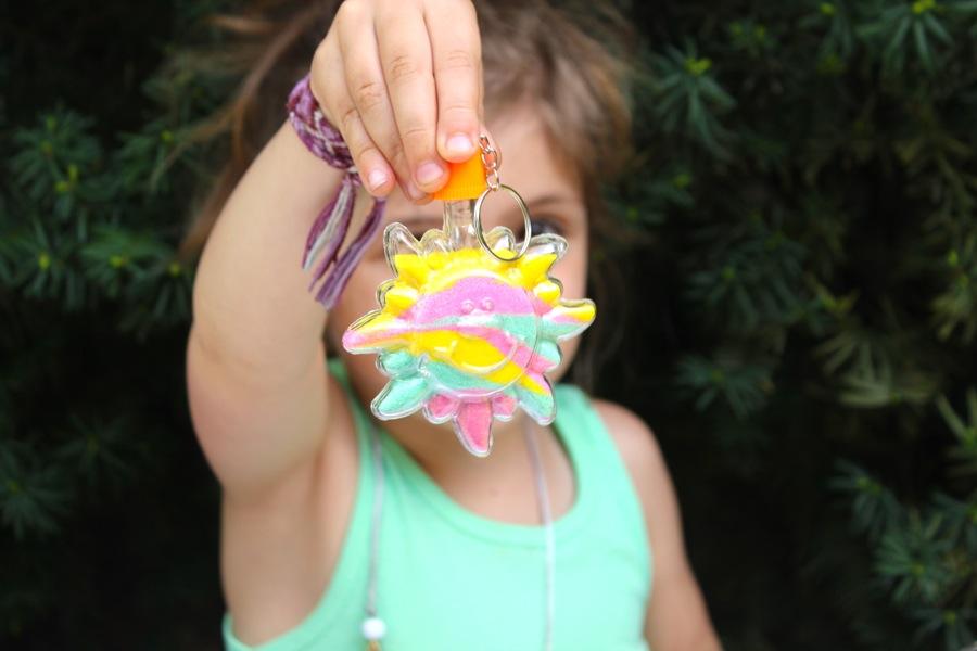 girl-holding-up-plastic-sun-for-sand-art