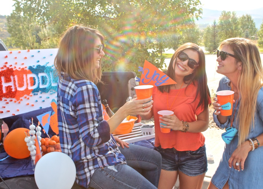 three-women-wearing-orange-and-blue-at-a-bronco-tailgate-party-with-a-yay-flag-and-pickup-truck
