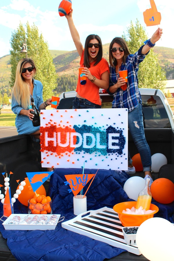 orange-and-blue-womens-tailgate-party-with-a-huddle-sign-and-pick-up-truck