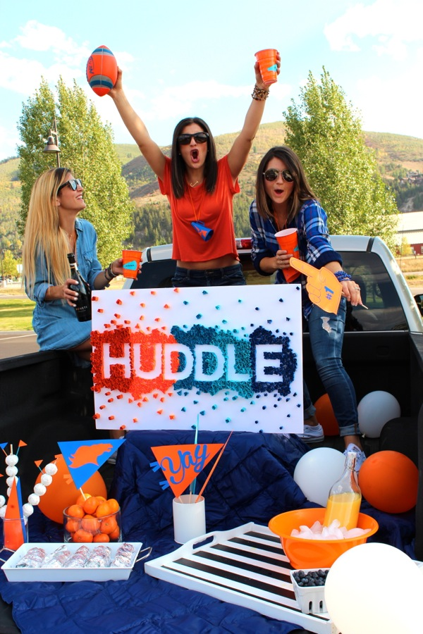 three-girls-in-a-pickup-truck-for-a-tailgate-party-holding-number-one-foam-fingers